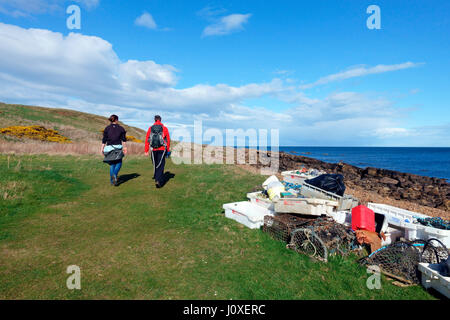 Walkers pass collected marine debris from a recent beach clean up on the Fife Coastal Path between Crail to Anstruther - Stock Photo