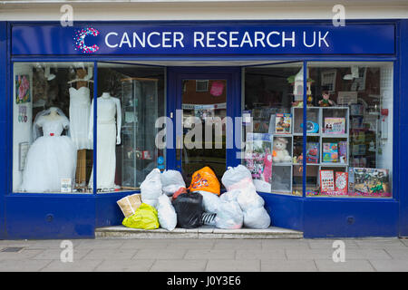 Cancer Research UK front of shop with plastic bags full of donations.