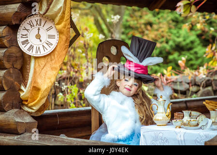 An little beautiful girl holding cylinder hat with ears like a rabbit over head at the table - Stock Photo
