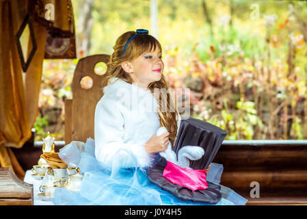 An little beautiful girl holding cylinder hat with ears like a rabbit in the hands at the table - Stock Photo