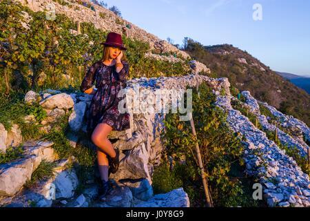 Young woman in traditional vineyard watching sunset atmospheric solo hope nostalgia nostalgic romantic wearing teenage - Stock Photo
