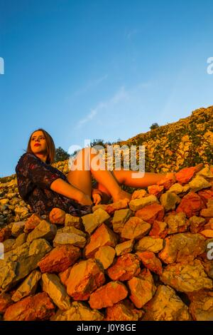 Pretty young woman in traditional vineyard atop stone wall watching sunset warm light clear blue sky free copy space - Stock Photo