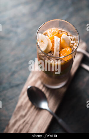 Smoothies with slices of banana, mandarin on a rustic pedestal vertical - Stock Photo