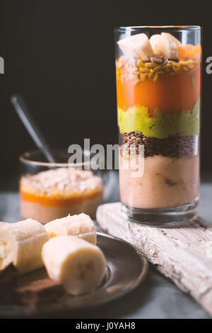 Banana smoothie, flax seed, avocado, pumpkin layers side view vertical - Stock Photo