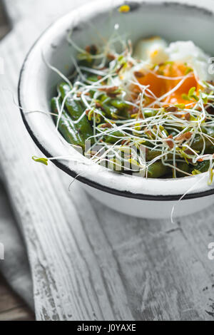 Salad with beans, sprouted flax and quail eggs on a wooden stand vertical - Stock Photo