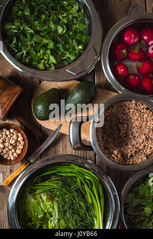 Buckwheat in a pot, green grass in the water and avocado on the table vertical - Stock Photo