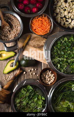 Vegetables in a bowl, chickpeas, avocado halves on the table vertical - Stock Photo