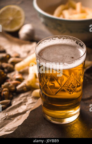 Glass of beer with blurred snack on the metal background - Stock Photo
