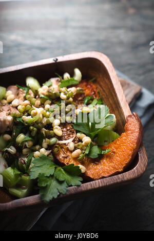 Baked pumpkin with mash and parsley in the wooden bowl - Stock Photo