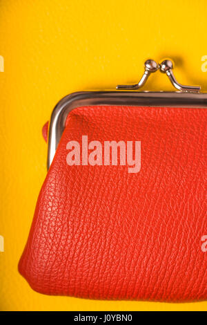 Orange purse on a wooden yellow table - Stock Photo