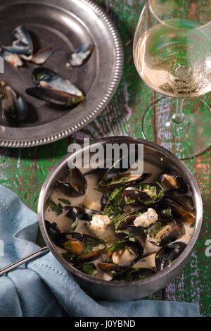 Mussels in leaves in sauce on a tin plate and in a saucepan - Stock Photo
