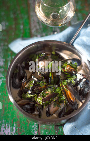 Mussels in sash in saucepan on boards - Stock Photo