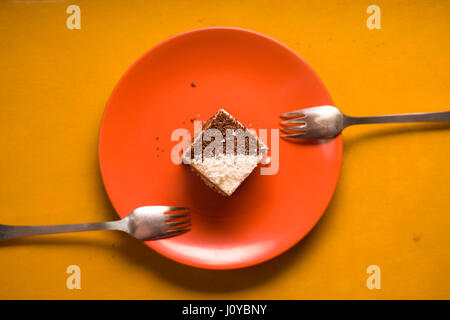 Chocolate cake with coconut chips on a ceramic plate - Stock Photo