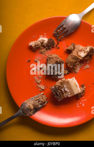 Pieces of chocolate cake with coconut chips on an orange plate - Stock Photo