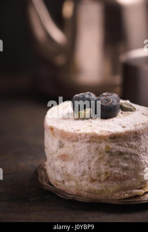 Cake with blueberries and pistachios against a teapot - Stock Photo