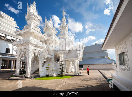 Woman in red costume in Wat Rong Khun The White Temple in Chiang Rai, Thailand - Stock Photo