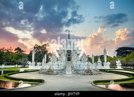 Wat Rong Khun The White Temple and pond at dramatic sunset background in Chiang Rai, Thailand - Stock Photo