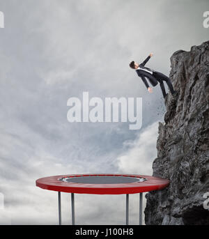 Businessman jumping on a trampoline to reach the flag. Achievement business goal and Difficult career concept - Stock Photo