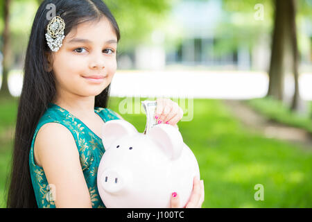 Closeup portrait, young lady holding piggy bank, isolated outdoors green grass and trees background. Money building - Stock Photo