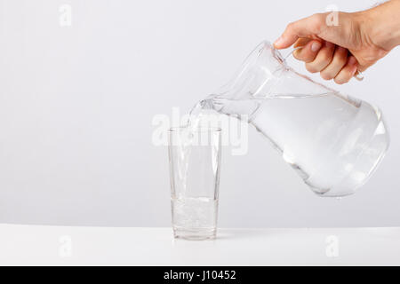Hand pouring water from glass jug to glass against white background - Stock Photo
