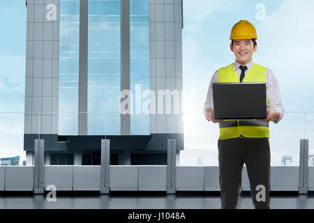 Handsome asian architect man with laptop wearing protective helmet standing in front of a skyscrapers building - Stock Photo