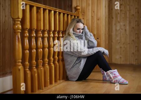 girl sitting on the floor near the wooden railing - Stock Photo