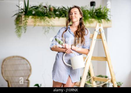 Woman on the ladder in orangery - Stock Photo