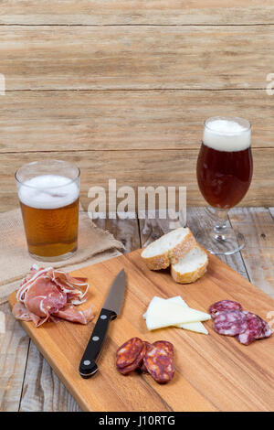 wooden board with sausage, cheese and beer glasses on an old wooden table - Stock Photo