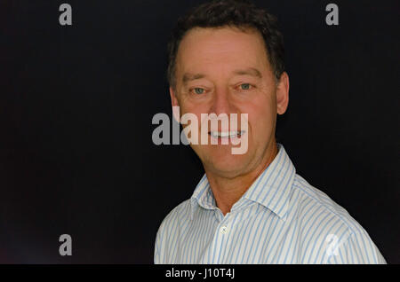 A photo of a white male in his 50's dressed for business and smart casual - Stock Photo