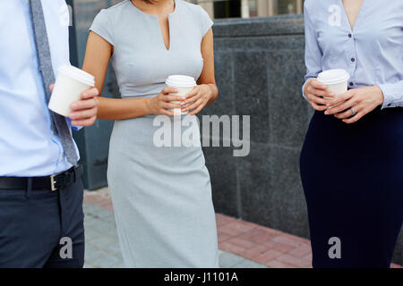 Mid section shot, group of business people standing outside modern office building talking and holding paper coffee - Stock Photo