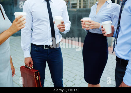Mid section shot, group of unrecognizable business people standing outside modern office building talking and holding - Stock Photo