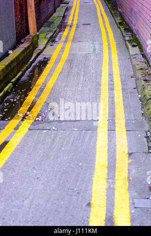 Double yellow lines down both sides of a very narrow road. - Stock Photo