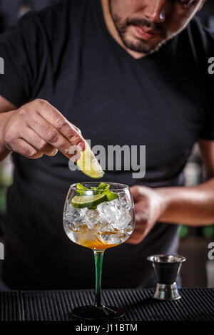 Bartender putting lime into glass, barman preparing cocktail - Stock Photo