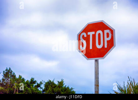Stop road sign against cloudy sky. - Stock Photo