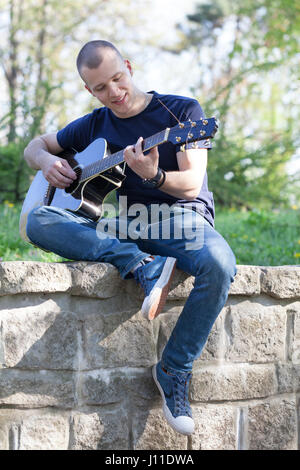 Handsome young man enjoying the park with a guitar.Selective focus and small depth of field. - Stock Photo