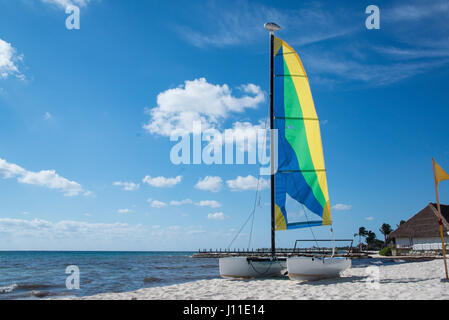 Colorful sail and sailboat catamaran is pulled up and docked on sandy beach in Mexican Caribbean on a bright sunny - Stock Photo