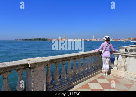 Venice, Italy, 08 April 2017, Travel to Venice, ​ Young traveler woman in a hat stands leaning on old balustrade - Stock Photo