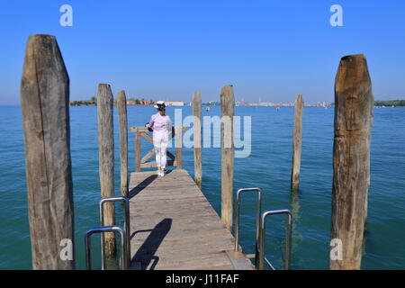 ​ Venice, Italy, 08 April 2017, Travel to Venice, ​ Young woman in a hat stands on a wooden platform and looks at - Stock Photo