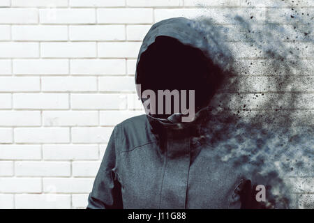 Thinking mind blowing thoughts, faceless hooded person against white brick wall - Stock Photo