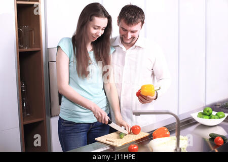 Portrait of happy young couple cooking together in the kitchen. - Stock Photo