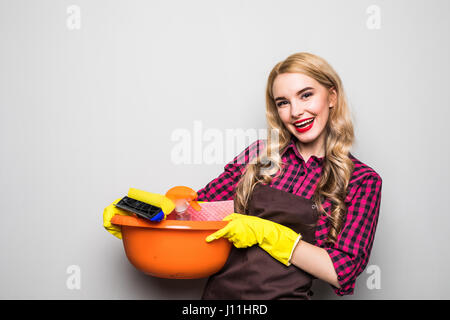 Young woman holding cleaning tools and products in bucket, isolated on white - Stock Photo