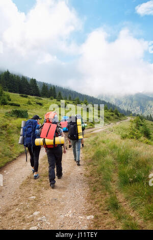 group of hikers with backpacks on a path through the forest in the mountains. Active holidays. Tourists trekking - Stock Photo