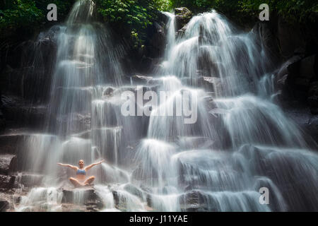 Travel in Bali jungle. Beautiful young woman sitting in yoga pose on rock under falling spring water, enjoy tropic - Stock Photo
