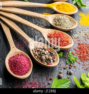 Assortment of spices in the wooden spoons. - Stock Photo