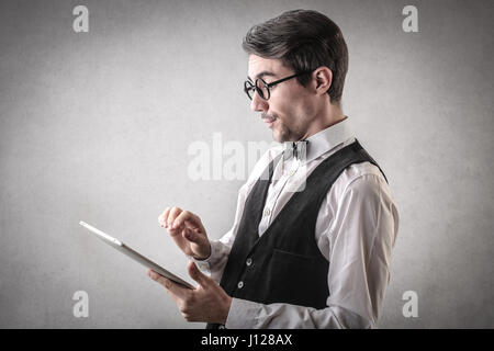 Focused elegant man using tablet - Stock Photo