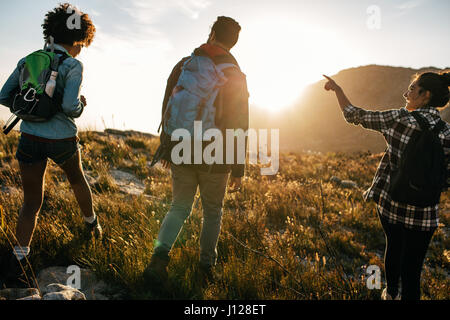 Rear view shot of young people on countryside hiking. Group of hikers walking on hill on a summer day. - Stock Photo