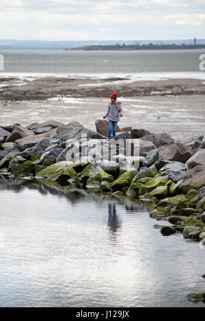 Child playing on the rocks bordering the Three Shells Beach Lagoon on Western Esplanade, Southend on Sea, Essex. - Stock Photo