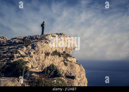 Man standing on cliff - Stock Photo