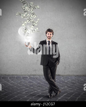 Businessman with lightbulb, money coming out of it - Stock Photo