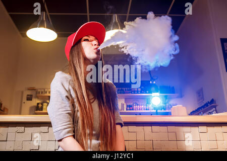 Young pretty woman in red cap smoke an electronic cigarette at the vape shop - Stock Photo